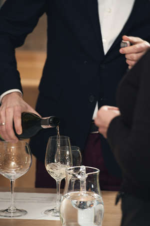 sommelier pouring wine into glass at wine tasting