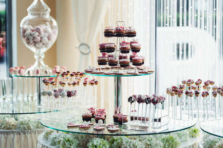 banket: Cute candy bar with various candies and cakes. Wedding candybar