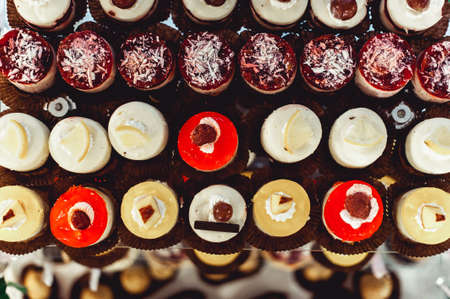 rows of italian mignon cakes on a glass stand Stock Photo