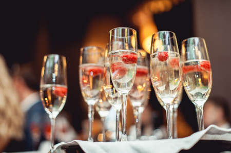 few champagne glasses wich raspberries. wediing party Foto de archivo