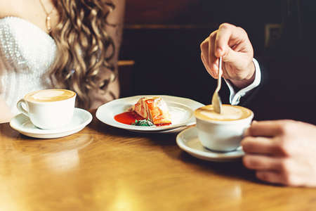 the bride and groom drinking coffee and eating cake in a cafe at the wooden table Stock Photo