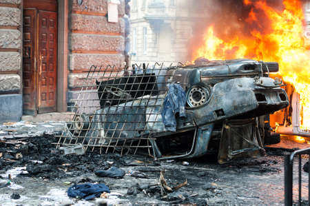 burning car. car destroyed and set on fire during the riots. city center