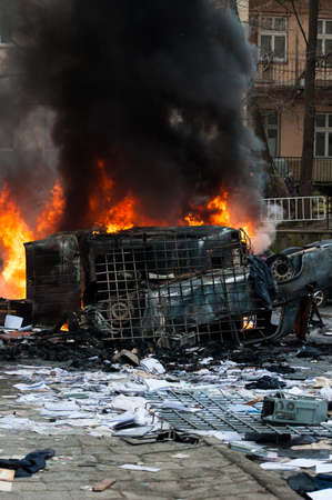 vandalism: burning car. car destroyed and set on fire during the riots. city center