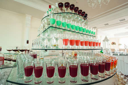 Variety of colorful green yellow and red alcohol shots in small glasses standing in row on a glass stand Stock Photo