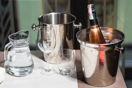 gold capped: Bottle of champagne in bucket in a restaurant