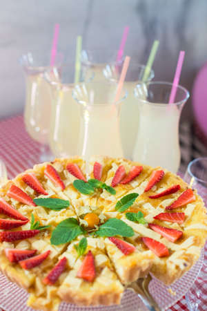 Whole round apple pie decorated with strawberry on a glass stand