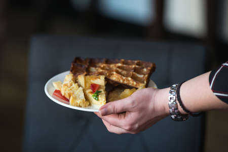 woman is going to eat Belgian waffles, brunch in a restaurant. plate in hand Stock Photo