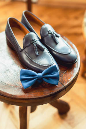 Blue shoes and bow tie on a wooden round stool. Accessory for formal dress. Symbol of elegance and fashion for men.