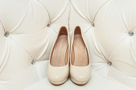 commit: brides biege shoes on heel on a leather vintage sofa
