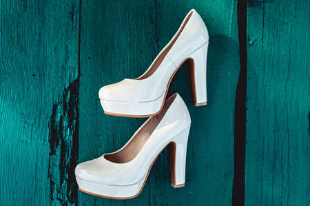commit: brides biege shoes on heel on a wooden board tiffany colour