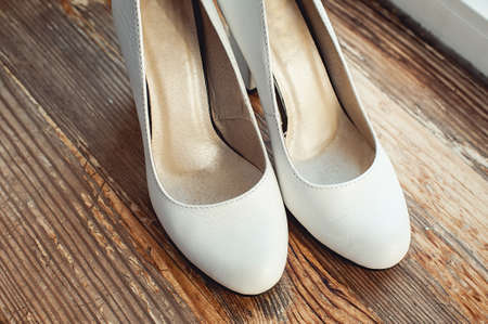 happynes: Beige Wedding shoes at the yellow rustic wooden floor with cracked paint Stock Photo