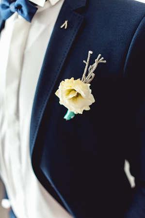 Details der männlichen Hochzeitskleidung. Schöner Boutonniere festgesteckt auf Mann im blauen Anzug, im weißen Hemd und in der blauen Fliege. Standard-Bild