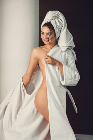 sexy young girl with dark hair, big eyes and dark eyebrows wearing white bath robe whith towel on her head.