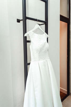 happynes: gorgeous white wedding dress on a fire ladder at the balcony. brides accessories in a wedding day