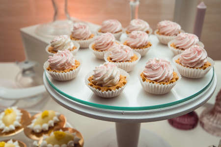 glass stand with cupcakes on a wedding candy bar table.