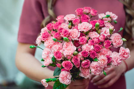 woman in a dress holding wedding bouquets of biege carnations an