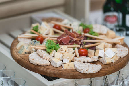 Mix cheese on wooden board with meat and bread