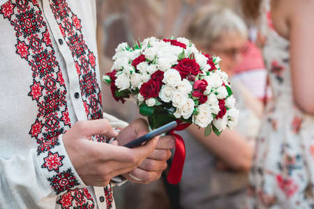 fiance hold in hand mobile phone and a wedding bouquet of biege and red roses. Wedding day