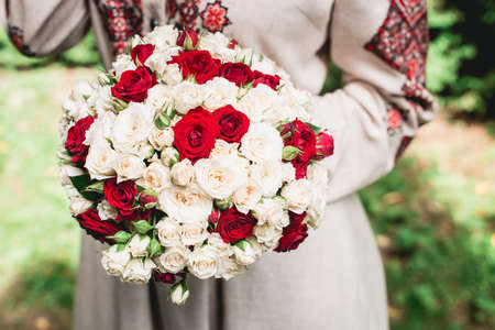 bride hold in hand wedding bouquet of biege and red roses.Wedding day