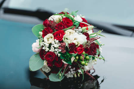 wedding bouquet of white and red roses on a reflectinle black car hood