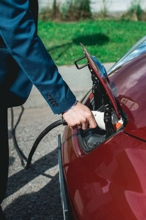 man charging battery of an electric car Stock Photo