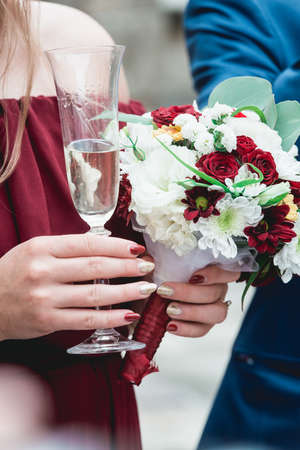 Girl in a pomegranate dress and with red manicure holding in her hands glass with champagne