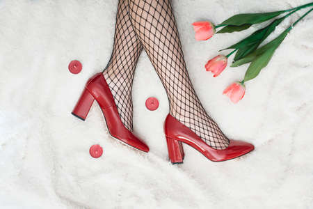 Sexy female legs in high heel red shoes and fishnet stockings. Retro style Stock Photo - 95437116