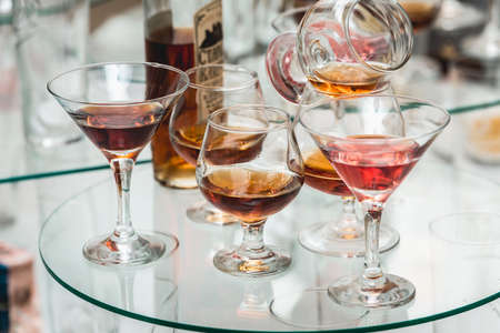 Different alcohol drinks on a glass stand. wine, champagne, cognac, vodka, martini