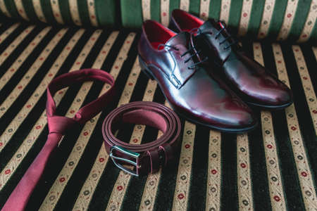 belt, necktie and shoes on a vintage sofa Stock Photo