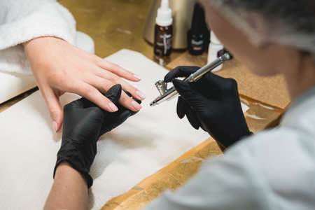 Closeup shot of a woman in a nail salon receiving a manicure by a beautician with airbrush. Woman getting nail manicure.