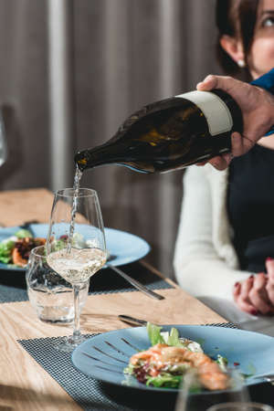 sommelier pouring champagne into glass at wine tasting Stock Photo