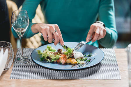 woman eats delicious salmon salad with egg in a restaurant. small portion