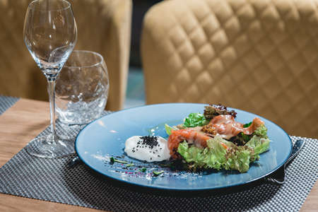 delicious salmon salad with egg in a restaurant. small portion