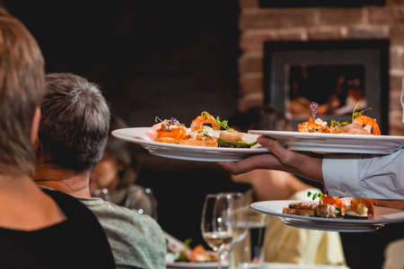 Waiter serves dish for food and wine tasting. Snacks with shrimp, fish fillets, Spain tapas recipe food pintxos