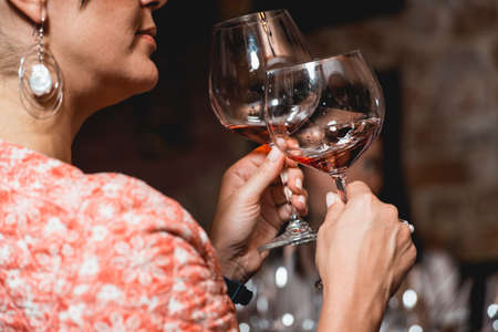 woman holds glass of wine. people consider the color of the wine and try how it smells in different glasses