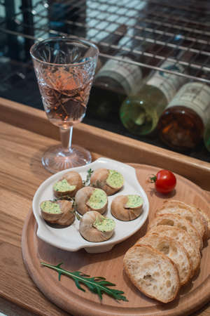 Snails with herbs butter, in traditional ceramic pan bread on a wooden plank. Glass of wine