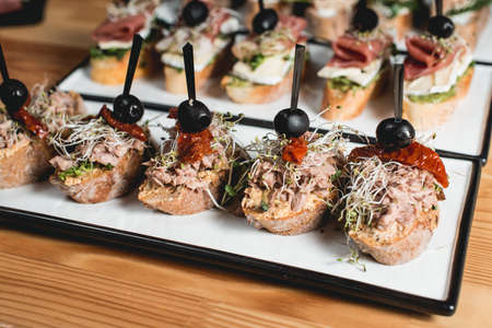 tasty pinchos with tuna, dried tomatoes, olive and pesto sauce, traditional spanish snack, served on a white plate
