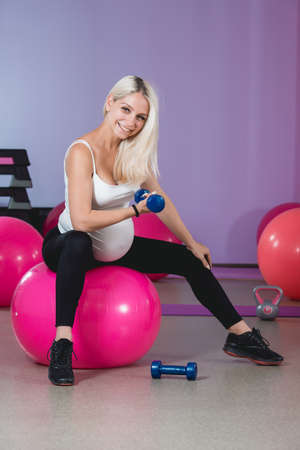 Attractive pregnant woman's doing exercises in the gym with dumbbells, healthy lifestyle