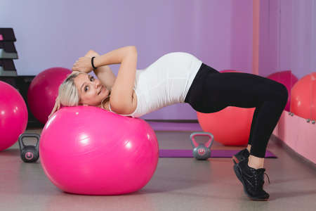 Pregnant woman in the gym lying on the ball relaxing after training to keep fit yourself