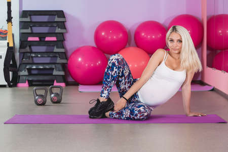 Pregnant woman in the gym sitting on the mat relaxing after training to keep fit yourself