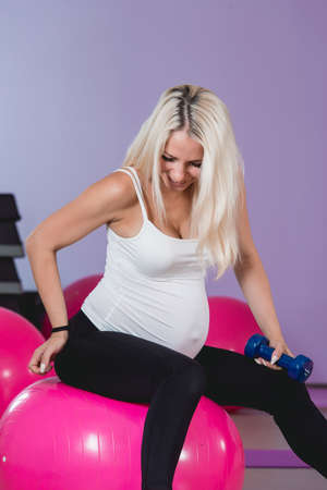 Sport training gym and health problem. Young attractive pregnant fit female with backache. Woman suffering from back pain
