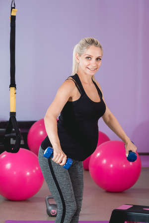Sporty woman doing exercises with a step aerobic. Photo of muscular female wearing sportswear on pink background. Strength and motivation