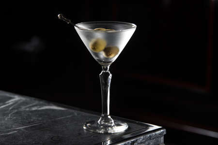Dry Martini cocktail on a bar desk. black background