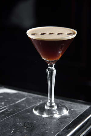 Espresso Martini cocktail on a bar desk. black background.