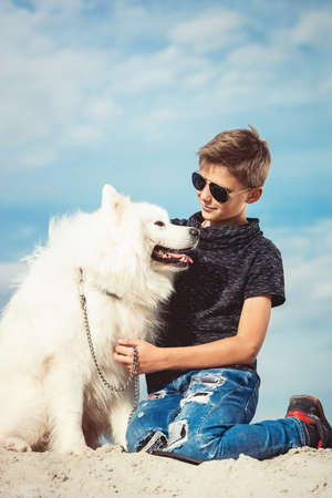 Happy 11 year old boy playing with his dog breed Samoyed at the seashore against a blue sky close up. Best friends rest and have fun on vacation, play in the sand