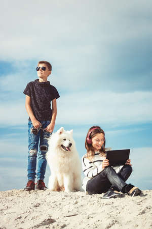 Happy 11 year old boy withhis dog breed Samoyed at the seashore against a blue sky close up. Best friends rest and have fun on vacation, play in the sand