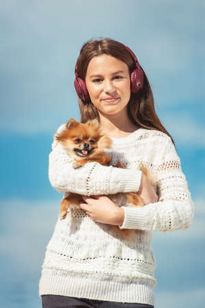 14 years girl in a wireless headphones listening to a music from a smart phone on a beach. against a blue sky. close up