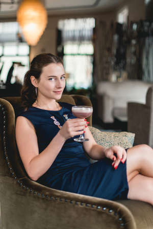 Fashionable gorgeous girl in a dark blue dress drinking cocktail in a luxery hotel lobby bar