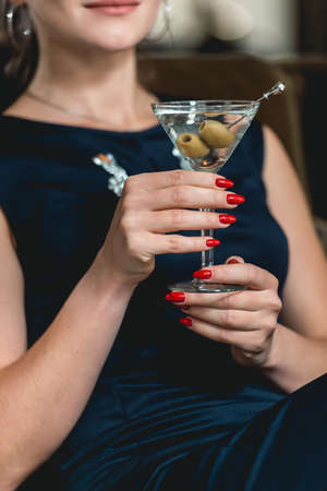 Dry Martini cocktail in womans hands with red manicure. Luxery hotel lobby bar. Stock Photo