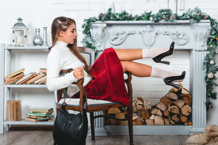 Wunderschöne junge Frau in einem roten Rock und weißem Pullover, die im Retro-Sessel auf einem weihnachtlich dekorierten Wandhintergrund sitzt. Erotische Beine in weißen Socken und schwarzen Lack High Heels